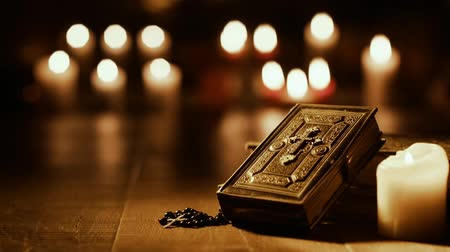 ciltli : Antique Holy Bible and sacred books in the church with candles in the background: religion and spirituality concept