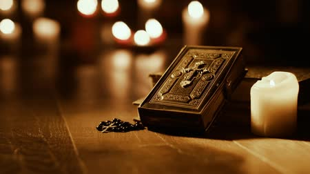 cristianity : Antique Holy Bible and sacred books in the church with candles in the background: religion and spirituality concept