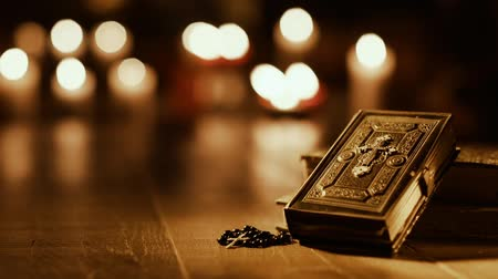 cristianity : Antique Holy Bible and sacred books in the church with candles in the background: religion and faith concept