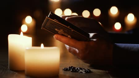 ciltli : Man reading the Holy Bible and praying in the Church with lit candles, religion and faith concept