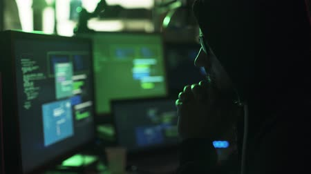 operational system : Nerd hacker with hoodie working at desk late at night, he is watching multiple screens and hacking networks, cyber security concept