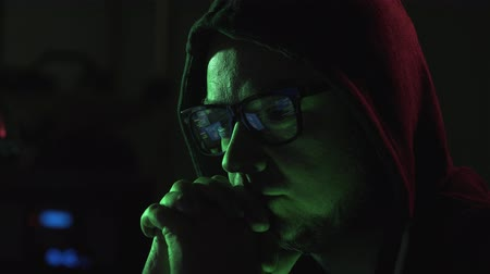 operational system : Hacker with glasses and hoodie, he is watching running on computer and shouting at camera, cyber crime and hacking concept Stock Footage