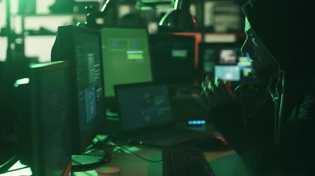 operational system : Black hat with hoodie working with multiple screens and hacking systems, cyber crime and security concept Stock Footage