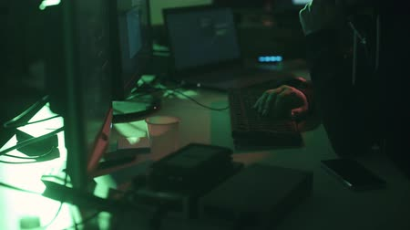 access : Black hat with hoodie working with multiple screens and hacking systems, cyber crime and security concept Stock Footage