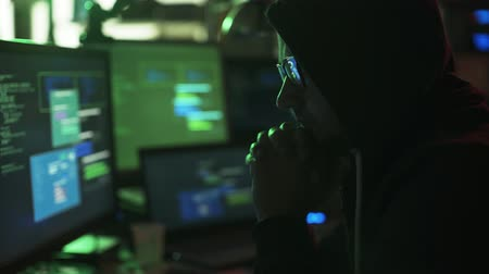 malware : Nerd hacker with hoodie working at desk late at night, he is watching multiple screens and hacking networks, cyber security concept