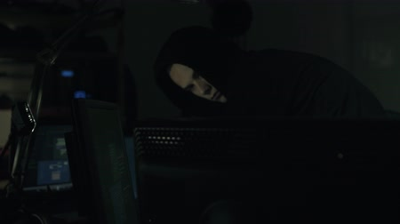 datas : Young hacker with hoodie connecting online with his computers, hacking and cyber crime concept