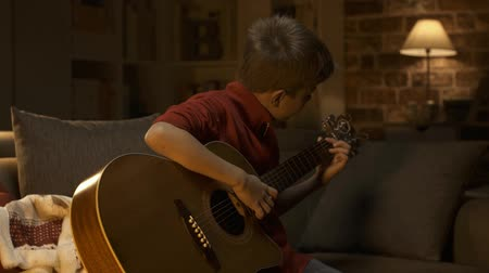 acoustic : Cute young boy sitting on sofa at home and playing guitar, music and childhood