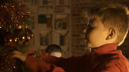вешать : Happy boy decorating his Christmas tree and hanging balls, his mother is sitting and smiling: holidays and family concept Стоковые видеозаписи