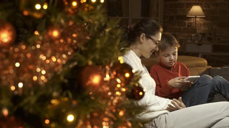 чат : Happy boy and mother using a digital tablet, Christmas tree with baubles in the foreground