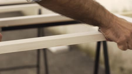 lakásfelújítás : Carpenter sanding and finishing a wooden frame, hands close up: DIY and woodwork concept Stock mozgókép