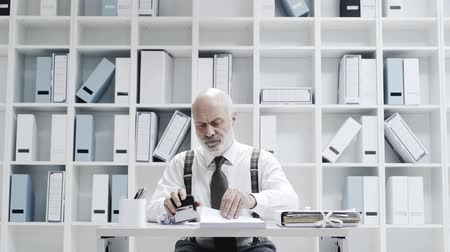 crumpled : Corporate businessman working in the office, they are throwing crumpled paper balls at him Stock Footage
