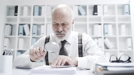 administrador : Senior business executive working in the office and carefully checking a contract using a magnifier