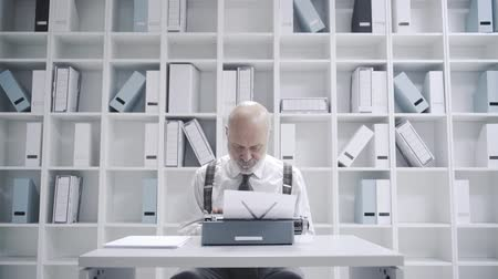 adminisztrátor : Corporate businessman working at his office with vintage typewriter, he is working slowly and getting tired, video montage