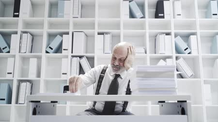 burocracia : Lazy office worker doing a repetitive dull job, he is stamping a pile of paperwork Stock Footage
