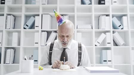 разочарование : Sad businessman celebrating a lonely birthday in the office, he is blowing a candle on a small cake