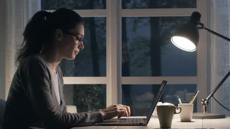 okno : Tired woman sitting at desk at home and working at laptop