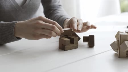 insight : Smart woman playing with an interlocking wooden puzzle, she is trying to solve it Stock Footage