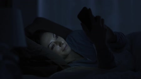 addicted : Stock photography Woman lying in bed late at night and chatting with her smartphone, tech addiction and social media concept