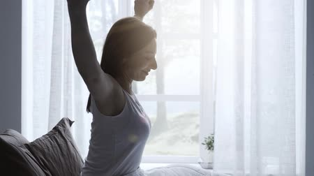 выражающий : Happy woman waking up in her bed, she is stretching her arms and smiling