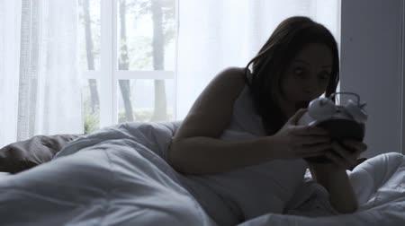 pánik : Panicked woman waking up late in the morning, she checks the time and gets up from bed quickly