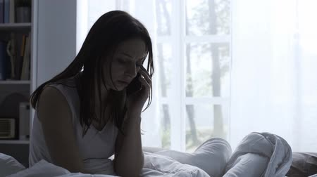 luto : She is sitting on the bed and crying Stock Footage