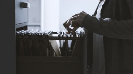 catalog : Female corporate secretary and businesswoman searching files in the filing cabinet, business and administration concept Stock Footage