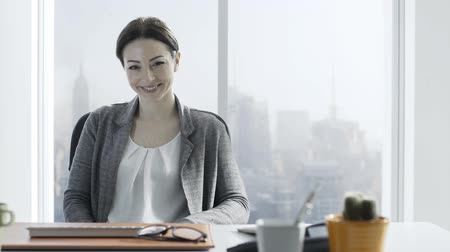 воротник : Confident young businesswoman sitting at desk talking on the phone Стоковые видеозаписи