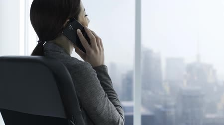 телефон доверия : Corporate businessman having a phone call in her office, she is looking at the window and nodding, business and communication concept