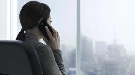 yardım hattı : Corporate businessman having a phone call in her office, she is looking at the window and nodding, business and communication concept