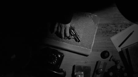 rivoltella : Noir film 1950s vintage gangster putting his revolver and fedora hat on the desktop, thriller and crime concept, flat lay desktop