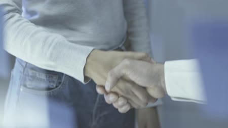 pracodawca : Executive giving handshake to young employee: employment, recruitment and partnership concept