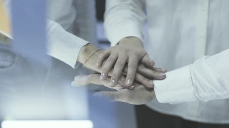 encouraging : Cheerful business team stacking hands together in the office: team spirit and teamwork concept Stock Footage