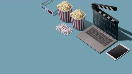 sinematografi : Online movie streaming and cinema: laptop with clapperboard as screen, popcorn and 3D glasses, blank copy space