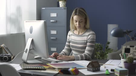 swatches : Young creative designer working at an office desk, she is typing and checking a house plan