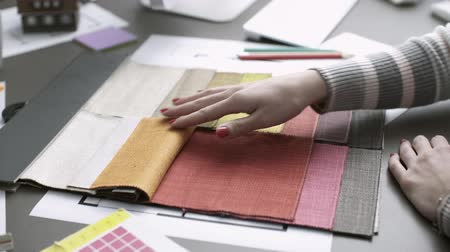 decorador : Interior designer working on a project and checking fabric samples, she is touching them and feeling the texture