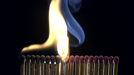 enxofre : Matches burning and lighting each other in a chain reaction, black background