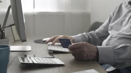 гражданин : Senior man doing online shopping and online banking, he is typing on the keyboard and entering credit card details