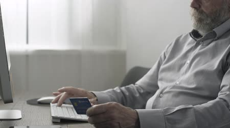 yaşlılar : Senior man doing online shopping and online banking, he is typing on the keyboard and entering credit card details