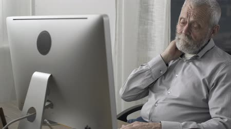 osteoarthritis : Senior man sitting at desk and having neck pain, aging and health concept
