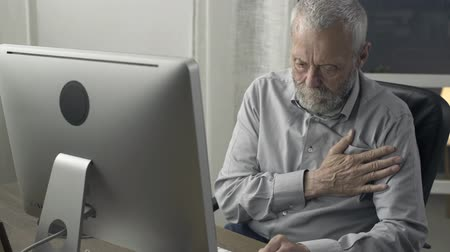 heart failure : Senior man sitting at desk and having heart attack, he is touching his chest and calling emergency services with his phone Stock Footage