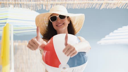 jóváhagyott : Cheerful beach girl holding inflatable ball and giving thumbs up, summer and vacations concept Stock mozgókép