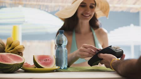fizetés : Young woman at the beach bar paying with a contactless credit card, technology and retail concept