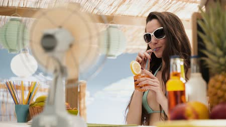 separè : Beautiful smiling girl with sunglasses, she is having a refreshing drink next to a beach bar kiosk, vacations and summer concept