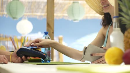 киоск : Young woman at the beach bar paying with a contactless credit card, technology and retail concept