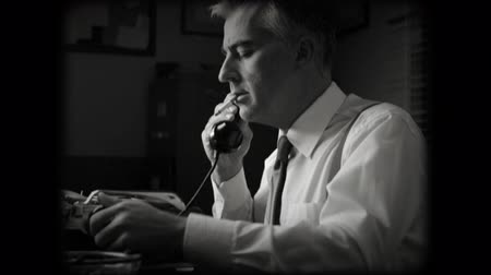 telephone handset : 1950s reporter working late at the desk, typing on a typewriter and having a phone call. Stock Footage