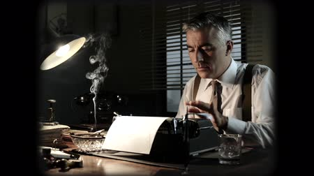 filmregisseur : Vintage journalist working late at night at office desk with typewriter and smoking a cigarette.