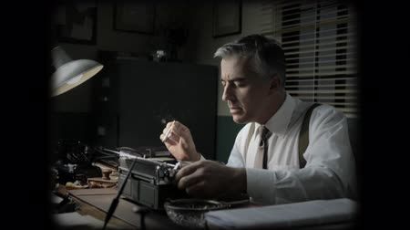 smokin : Vintage journalist working late at night at office desk, typing and smoking a cigarette.