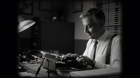 retro revival : Smiling vintage reporter working at office desk and typing on a typewriter.