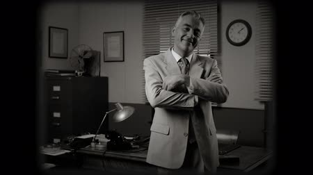 filmregisseur : Smiling businessman standing in front of his desk with arms crossed.