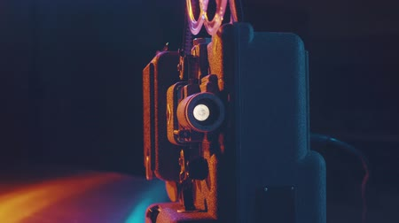 статья : Old fashioned movie projector and film screening in a dark room, colorful lights